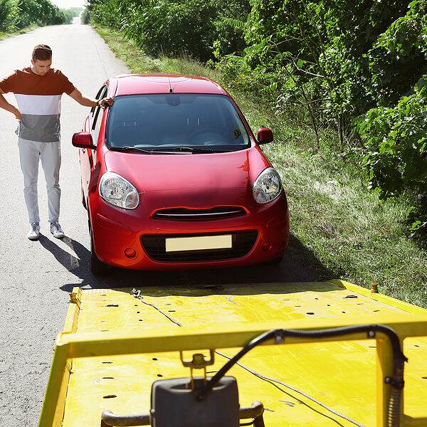 Man near broken car and tow truck on country road