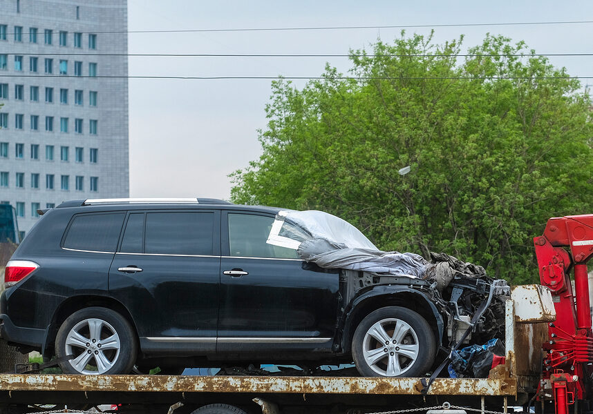 the image of the tow truck carrying the broken car